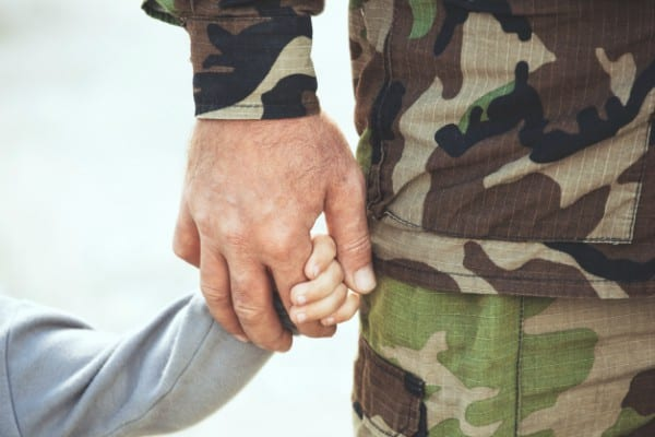 Military dad holding sons hand